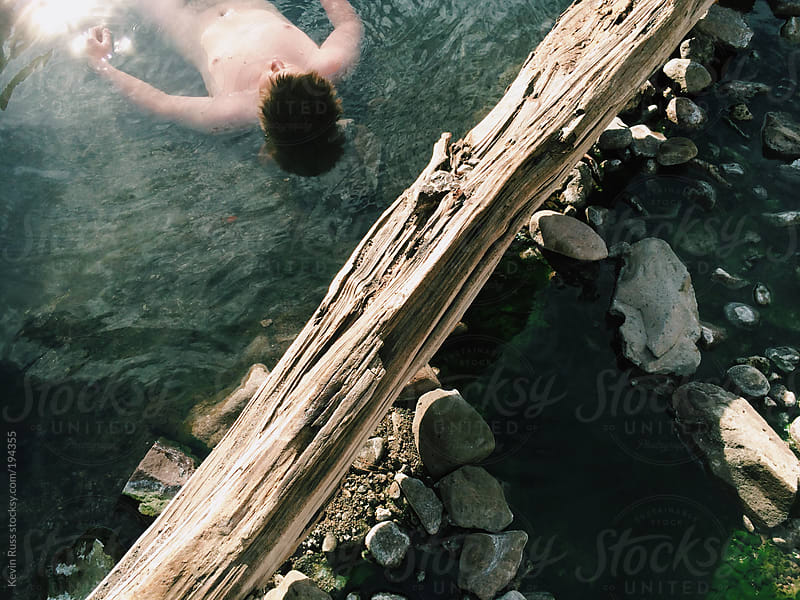 Man Floating in Hot Springs by Kevin Russ for Stocksy United