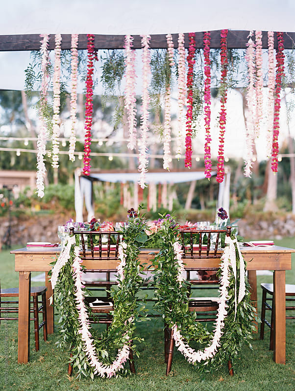 wedding table set up with hanging floral strings and floral decorated chairs by wendy laurel for Stocksy United