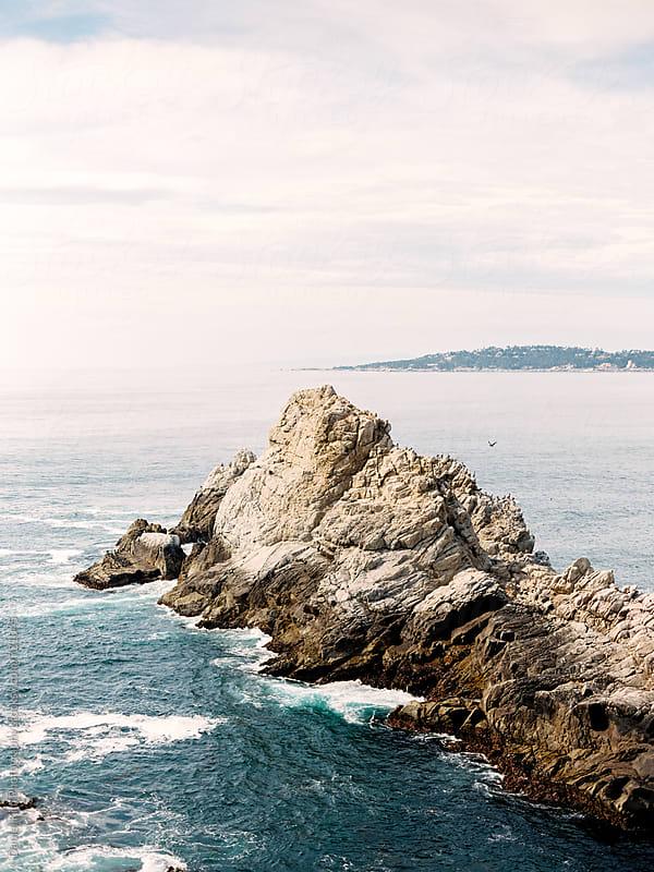 Rocky cliffs in ocean by Daniel Kim Photography for Stocksy United