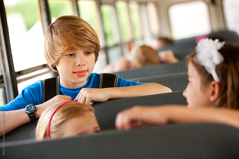 School Bus: Schoolboy Talking with Friends by Sean Locke for Stocksy United