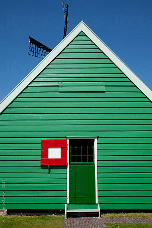 A green wooden house with a green door and a red shutter or hatch in the Netherlands by Ivo de Bruijn for Stocksy United