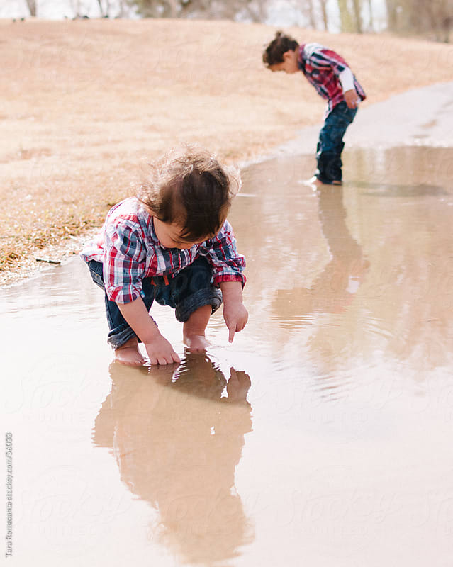 brothers studying a puddle by Tara Romasanta for Stocksy United