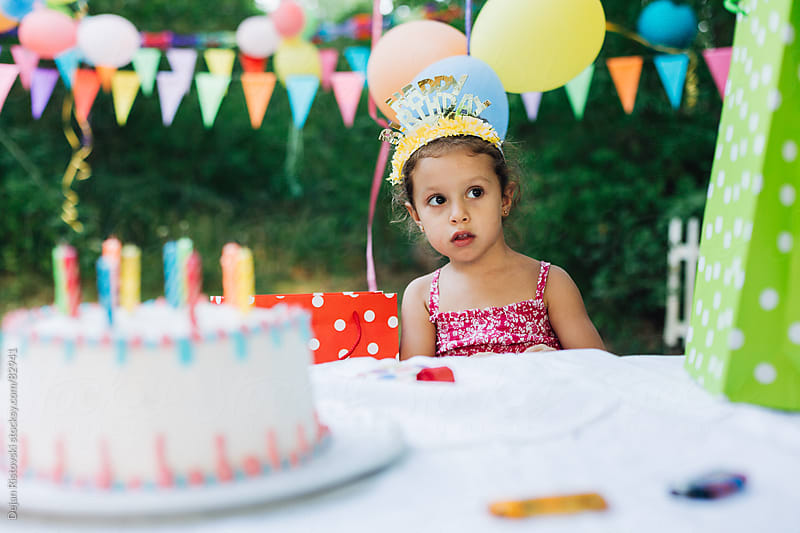 Child sitting on a birthday party by Dejan Ristovski for Stocksy United