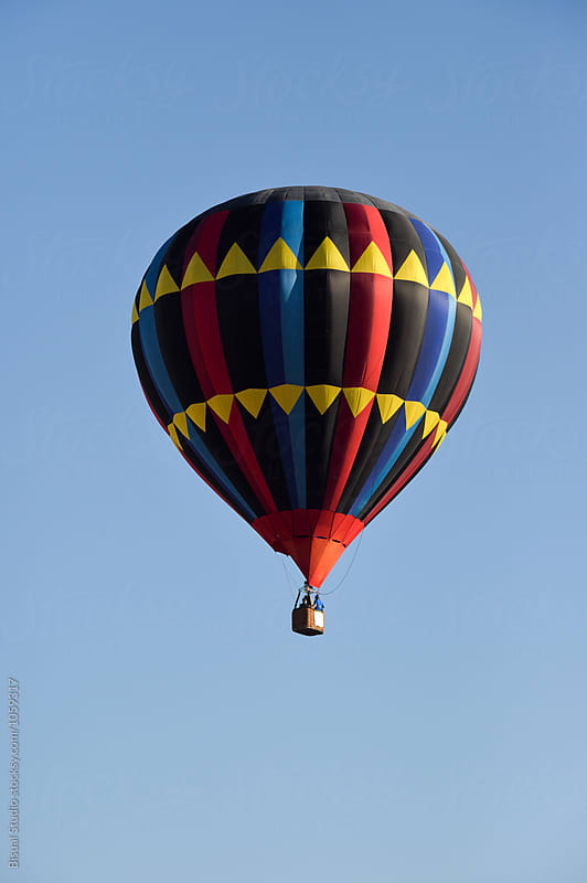 Hot air balloon fly over a blue sky by Bisual Studio for Stocksy United