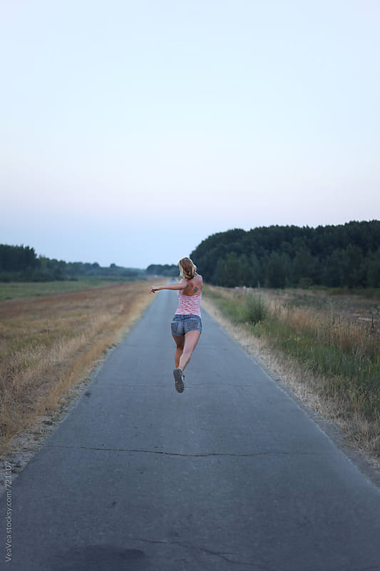 Young woman jumping on the road in the sunset by VeaVea for Stocksy United
