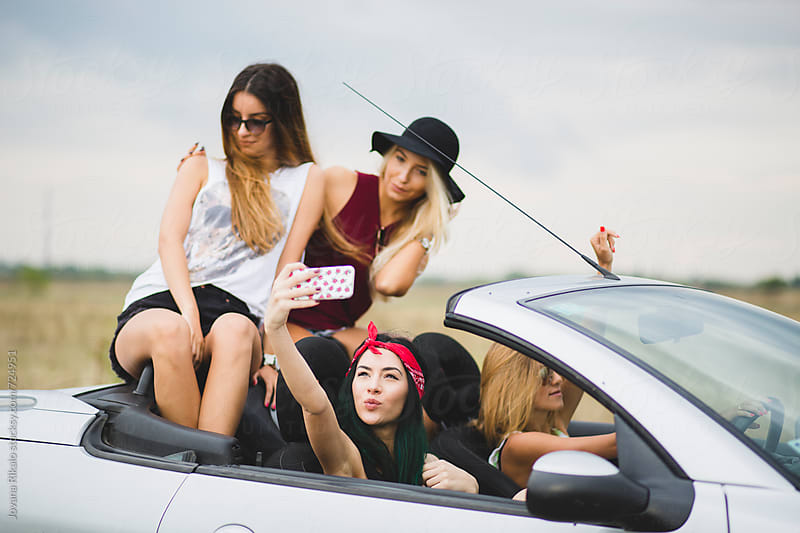 Happy female friends taking self-portrait in cabriolet by Jovana Rikalo for Stocksy United