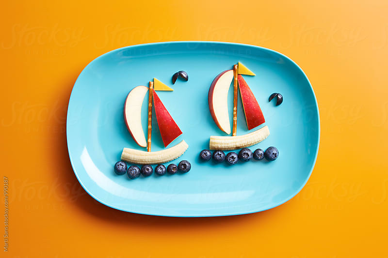 Blue plate with edible fruits and berries in form of boats by Martí Sans for Stocksy United