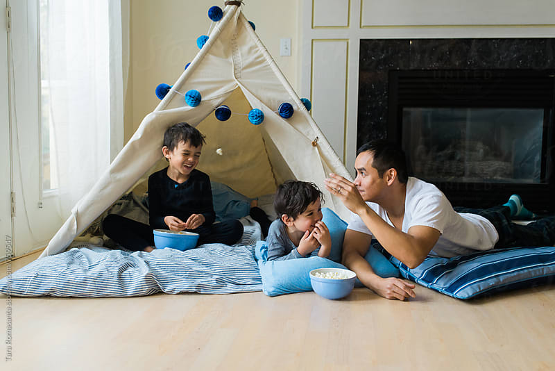father and two sons throwing popcorn by Tara Romasanta for Stocksy United