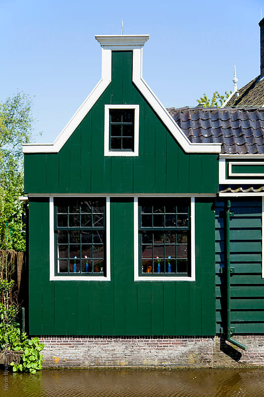 A green wooden house with white ornaments in the Netherlands with a small canal in front by Ivo de Bruijn for Stocksy United