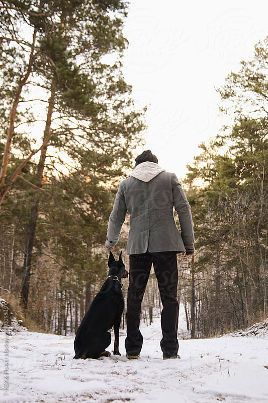 Man and Doberman in winter forest by Danil Nevsky for Stocksy United