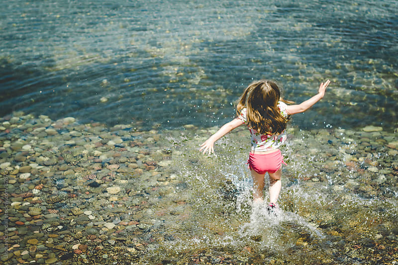 Girl running and splashing in a lake  by Lindsay Crandall for Stocksy United