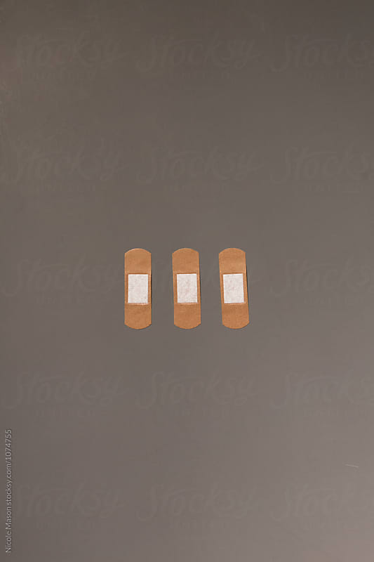 three fabric bandages on grey background by Nicole Mason for Stocksy United