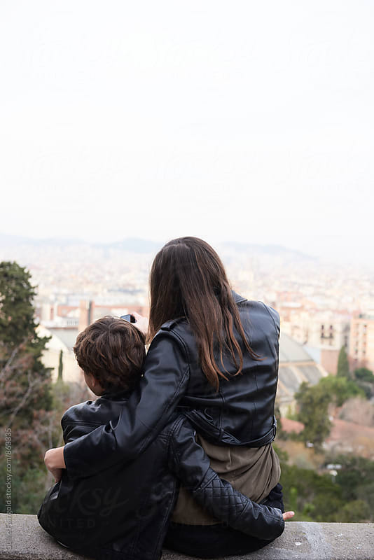 Back view of hugging sister and brother sitting in park. Barcelona by Guille Faingold for Stocksy United