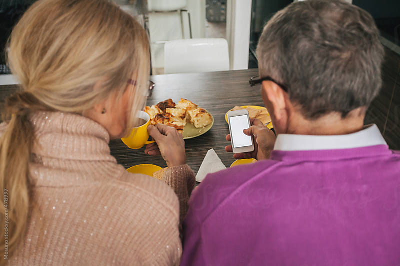 Senior Couple Using Technology During Breakfast  by Mosuno for Stocksy United