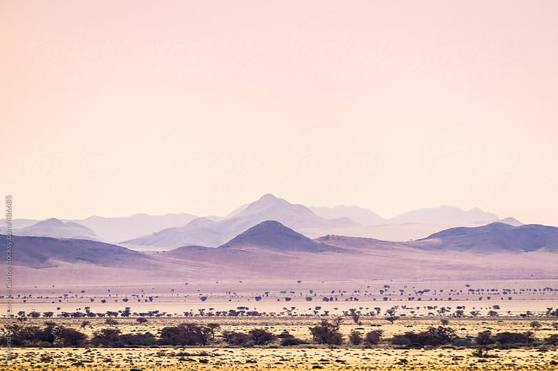 Hills landscape at sunset with purple haze by Alejandro Moreno de Carlos for Stocksy United