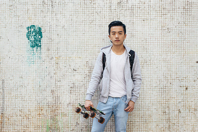 Casually Dressed Young Handsome Asian Man Holding Skateboard and Standing in Front of White Wall by VISUALSPECTRUM for Stocksy United