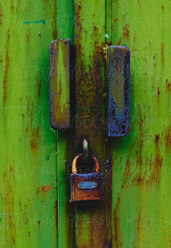 padlock on green door by Atakan-Erkut Uzun for Stocksy United