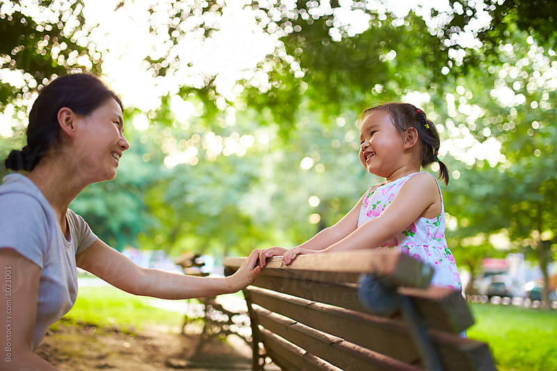 happy little asian girl with her mother in the park by cuiyan Liu for Stocksy United