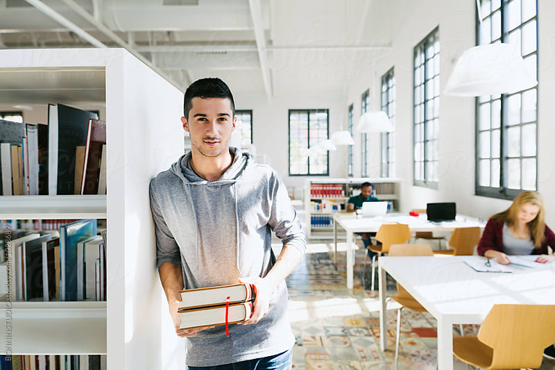 Young university man holidng books in a library. by BONNINSTUDIO for Stocksy United
