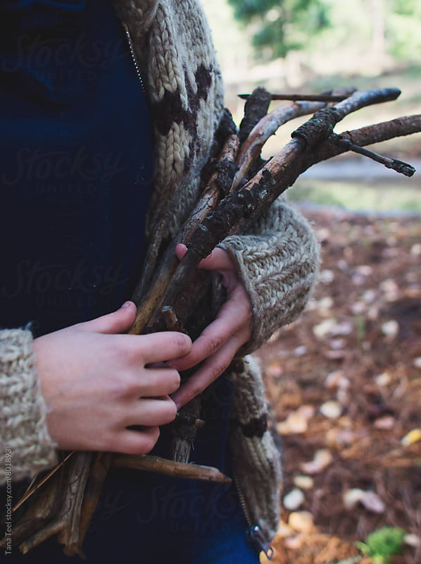 young woman holding gathered branches by Tana Teel for Stocksy United