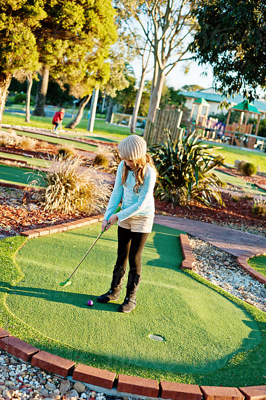 girl playing mini golf by Gillian Vann for Stocksy United