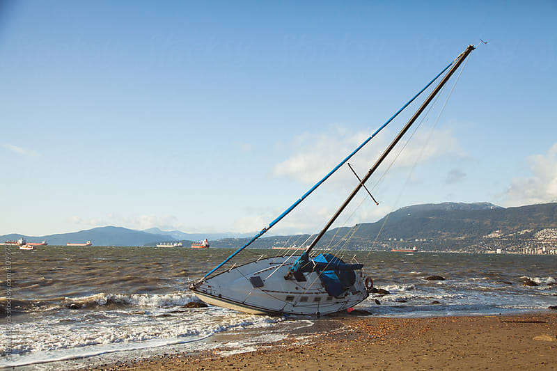A sail boat washes onto the shore during a big storm. by Cherish Bryck for Stocksy United