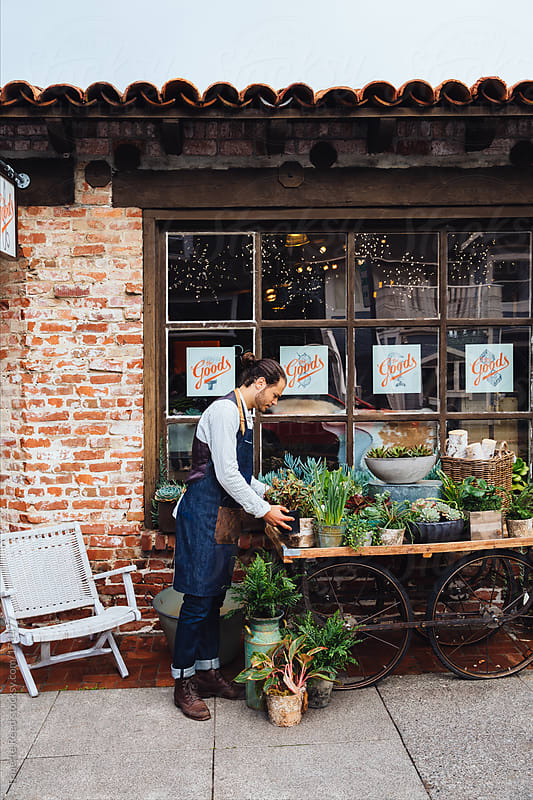 Small artisan business owner arranging plants in front of store by Trinette Reed for Stocksy United
