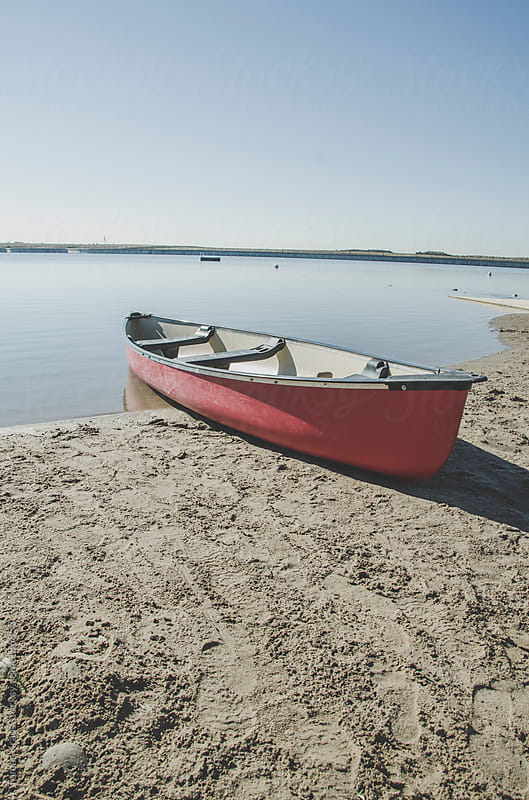 Red Canoe on a Beach by Tomas Kraus for Stocksy United