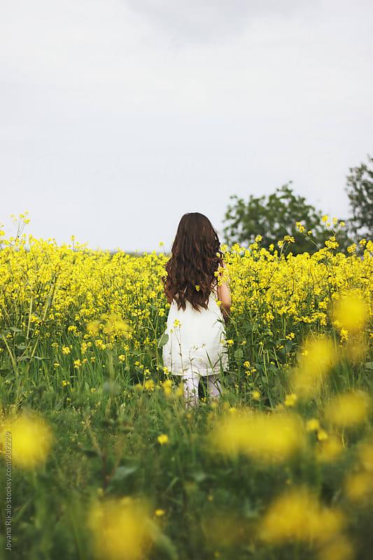 Cute little girl walking in a meadow by Jovana Rikalo for Stocksy United