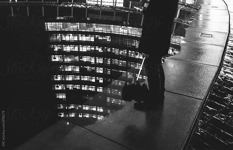 Man standing with phone against city reflection in a water puddle by GIC for Stocksy United