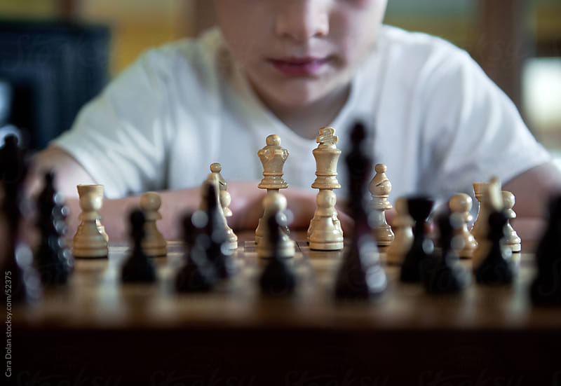 Boy playing game of chess decides his next move by Cara Slifka for Stocksy United
