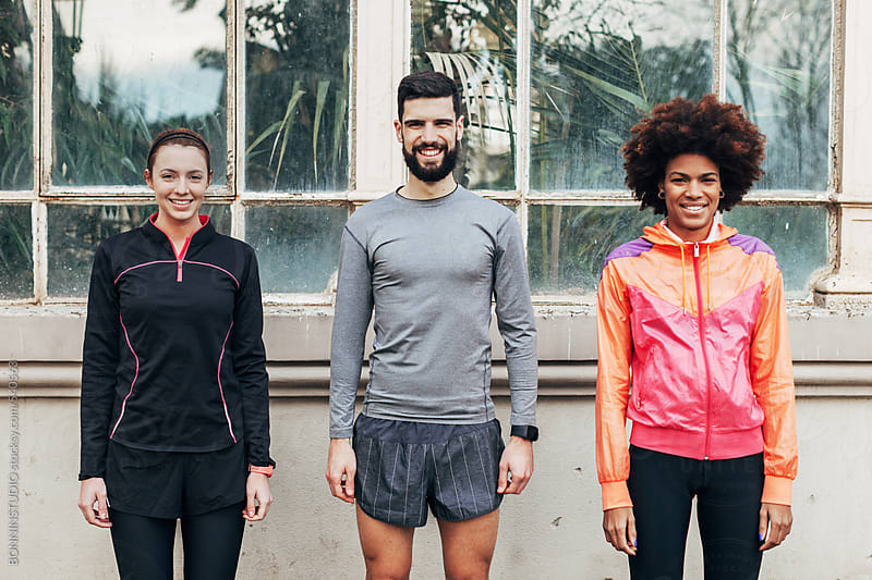 Portrait of group of runners standing in front a greenhouse. by BONNINSTUDIO for Stocksy United