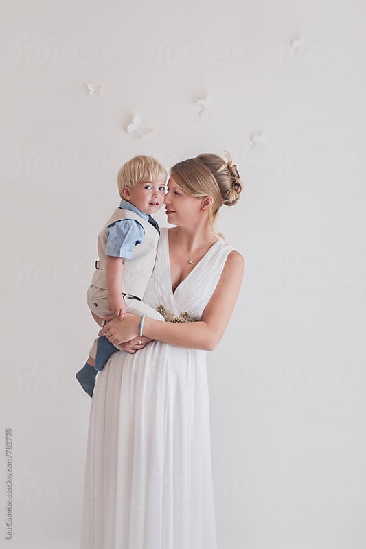 A beautiful stylish expectant mother holding her son in her arms by Lea Csontos for Stocksy United