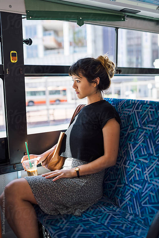 Young Japanese woman on a bus in Japan by Juri Pozzi for Stocksy United
