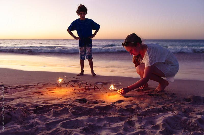 Boy looks on as a teenage girl lights sparklers at the beach after sunset by Angela Lumsden for Stocksy United