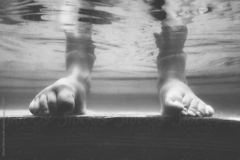Black and White Child's Feet Underwater by Alison Winterroth for Stocksy United