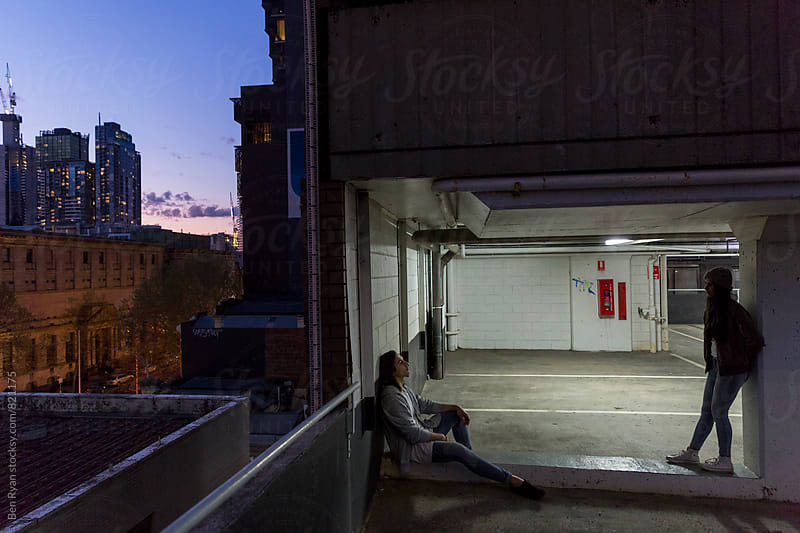 Young couple in rooftop carpark chatting backlit with city in background by Ben Ryan for Stocksy United