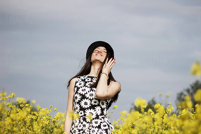 Portrait of a young woman with hat in a field by Jovana Rikalo for Stocksy United