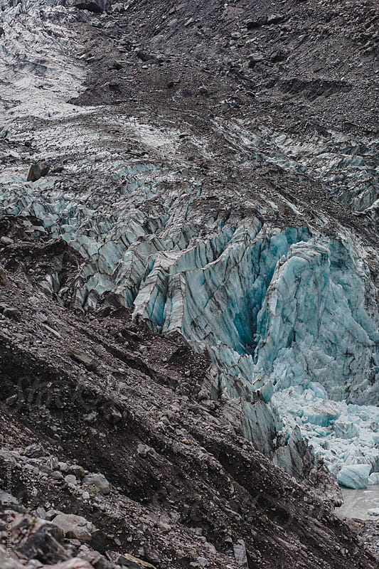 A glacier coming down from the mountain on a cloudy day by Leandro Crespi for Stocksy United