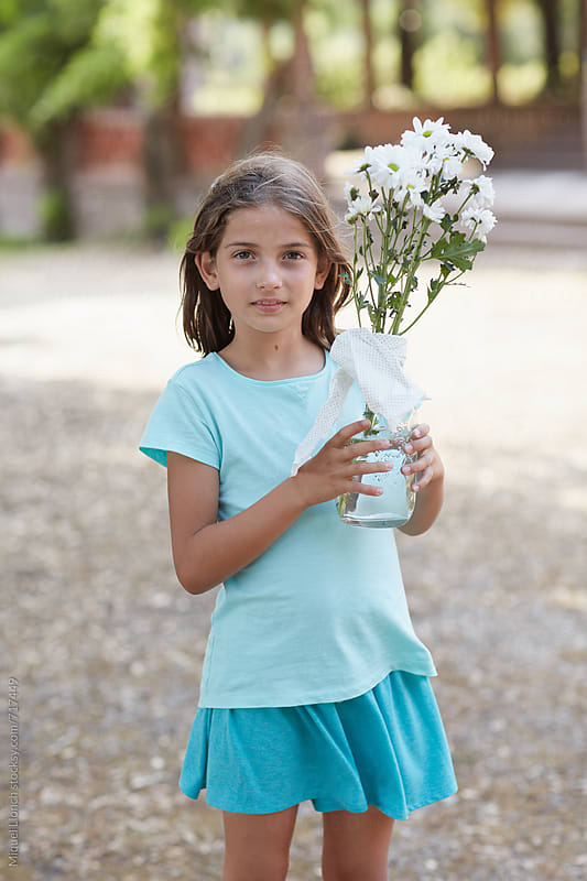 Portrait of a young girl with a jar and flowers by Miquel Llonch for Stocksy United