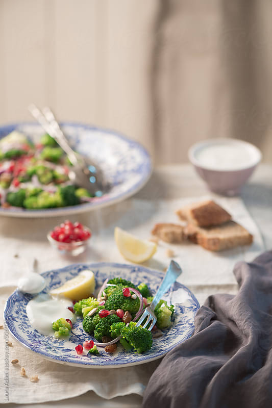 Broccoli salad with pomegranate seeds and raisins by Laura Adani for Stocksy United
