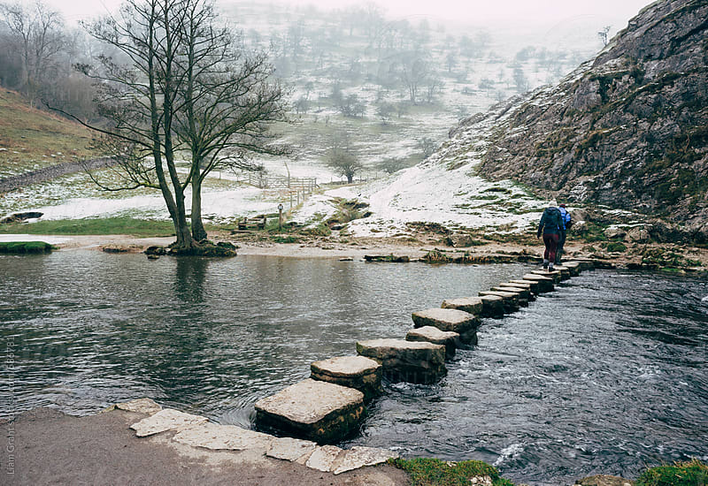 Young couple walk the stepping stones over the River Dove in Dovedale. by Liam Grant for Stocksy United