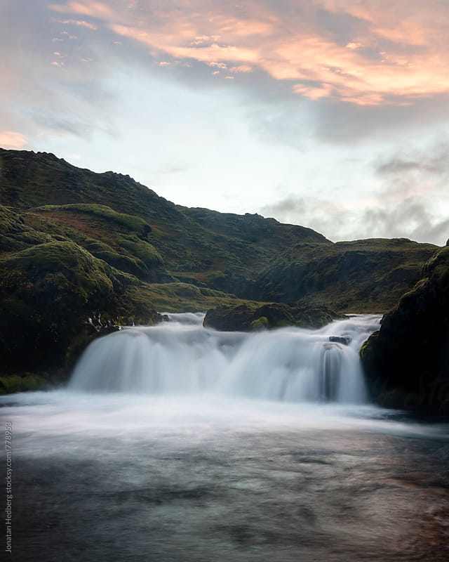 A waterfall at sunset by Jonatan Hedberg for Stocksy United