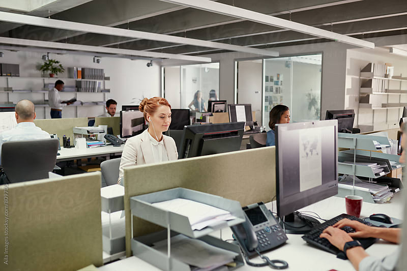 Young redhead business woman using earphones at office workstation by Aila Images for Stocksy United