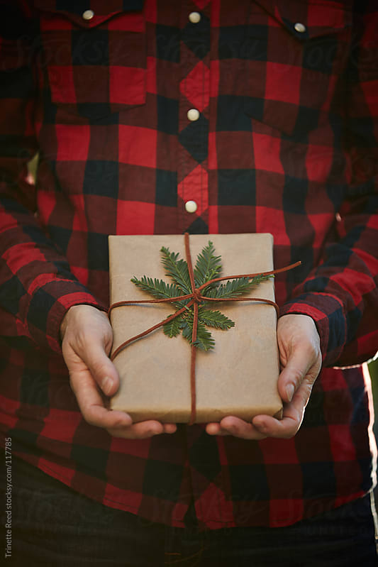 Man holding homemade wrapped Christmas Present by Trinette Reed for Stocksy United