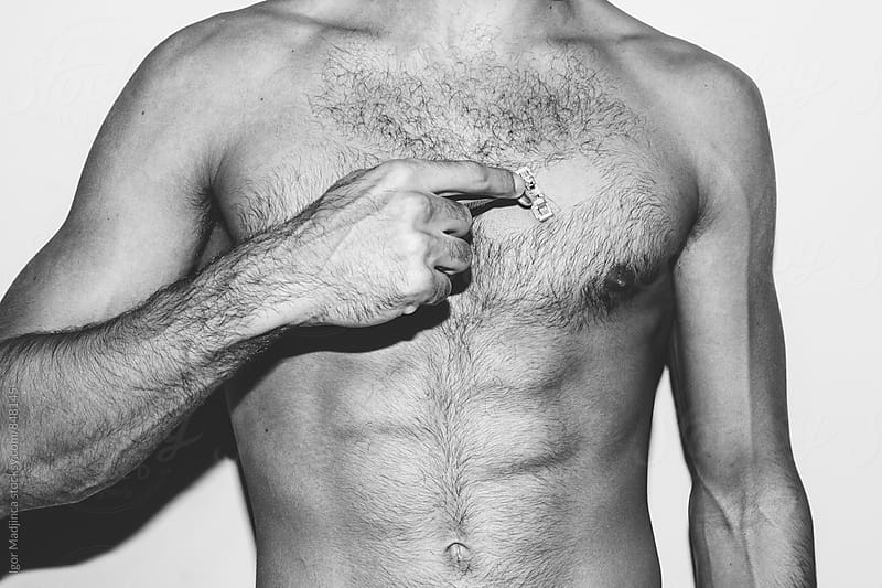handsome man shaving his chest with a razor by Igor Madjinca for Stocksy United