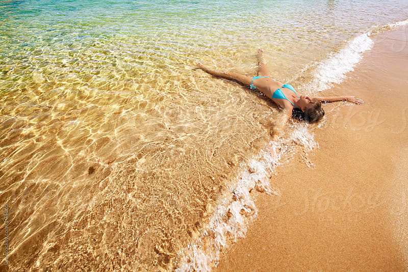 Young woman lying down in water on beach by Ilya for Stocksy United