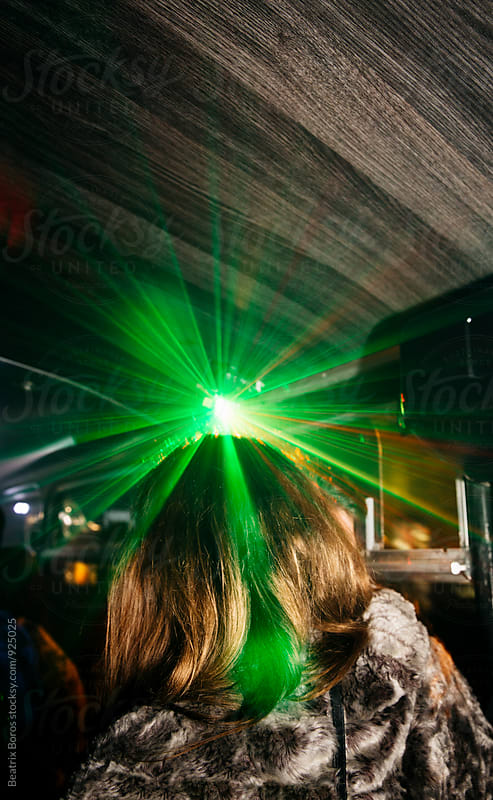 Woman in laser light beam from behind in a night club by Beatrix Boros for Stocksy United