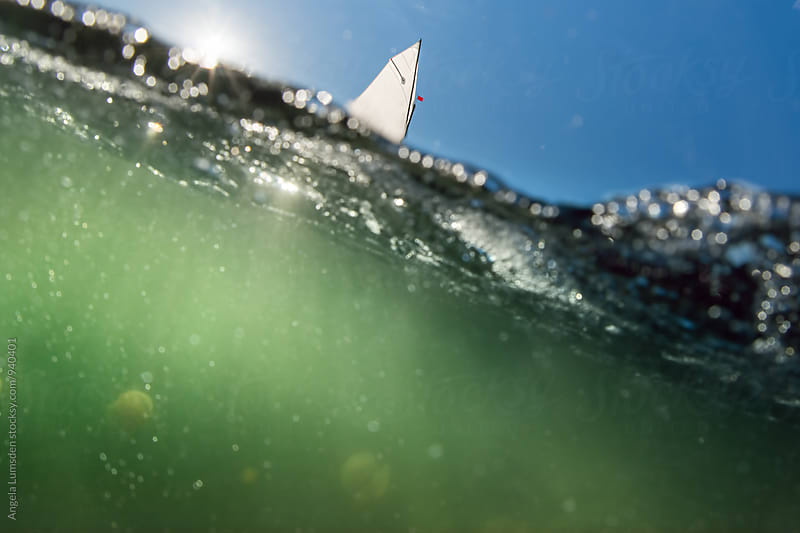 Split image of a optimist dinghy sail above light sparkling through water by Angela Lumsden for Stocksy United