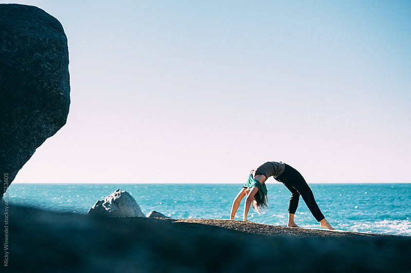 Young fit woman doing yoga on a rocky beach by Micky Wiswedel for Stocksy United